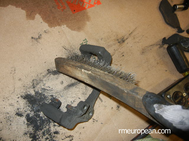 BMW E46 Brake Replacement - Cleaning the brake caliper bracket.